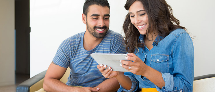 A couple at home compares CDs and Money Market Accounts on a tablet.