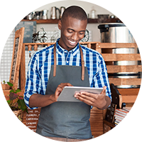 Young person wearing an apron smiles happily while tapping on his tablet.