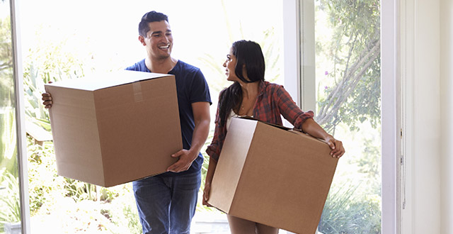 A young couple moves boxes into their new home.
