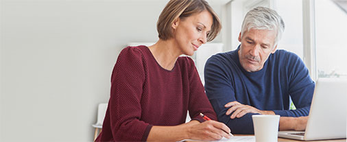 A couple reviews their finances on a laptop and paper as they consider refinancing their home.